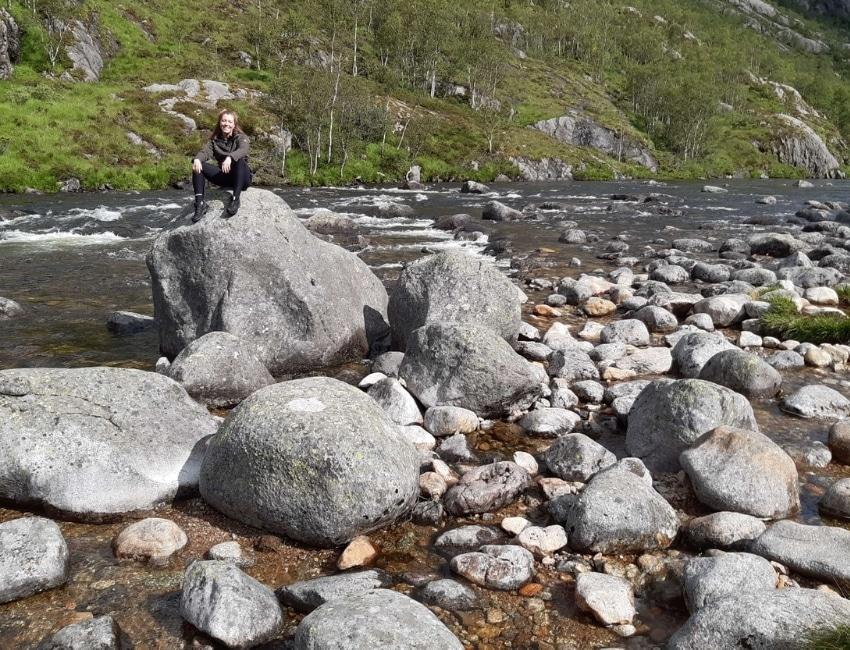 Anna Bregendahl sidder på en sten i en bæk
