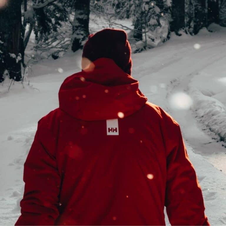 Mand der går i sne iført en outdoor jakke