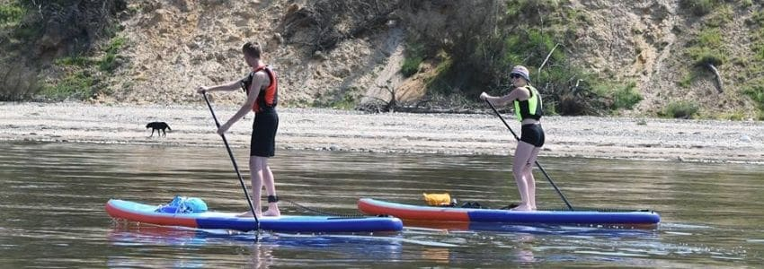 Kvinde i bikini der sidder på et paddleboard