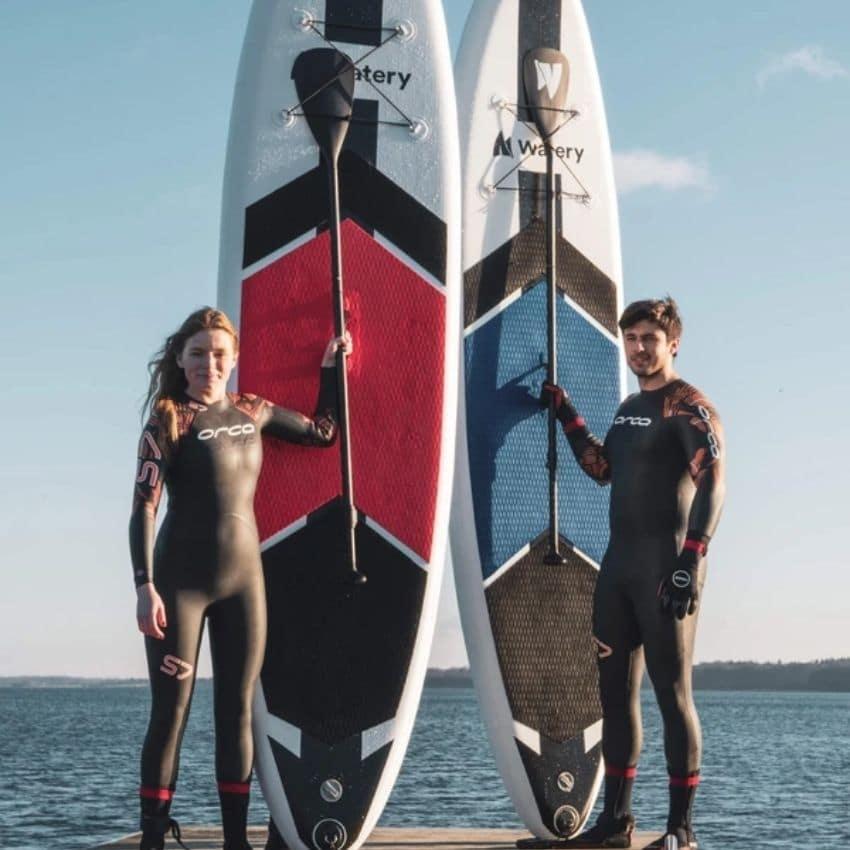Kvinde og mand der står med rødt og blåt paddleboard