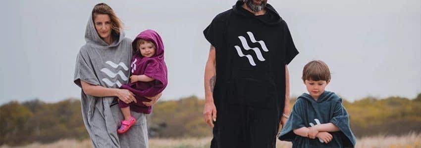 Familie i surf ponchoer