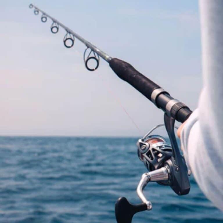 Mand der fisker på havet med teleskop fiskestang