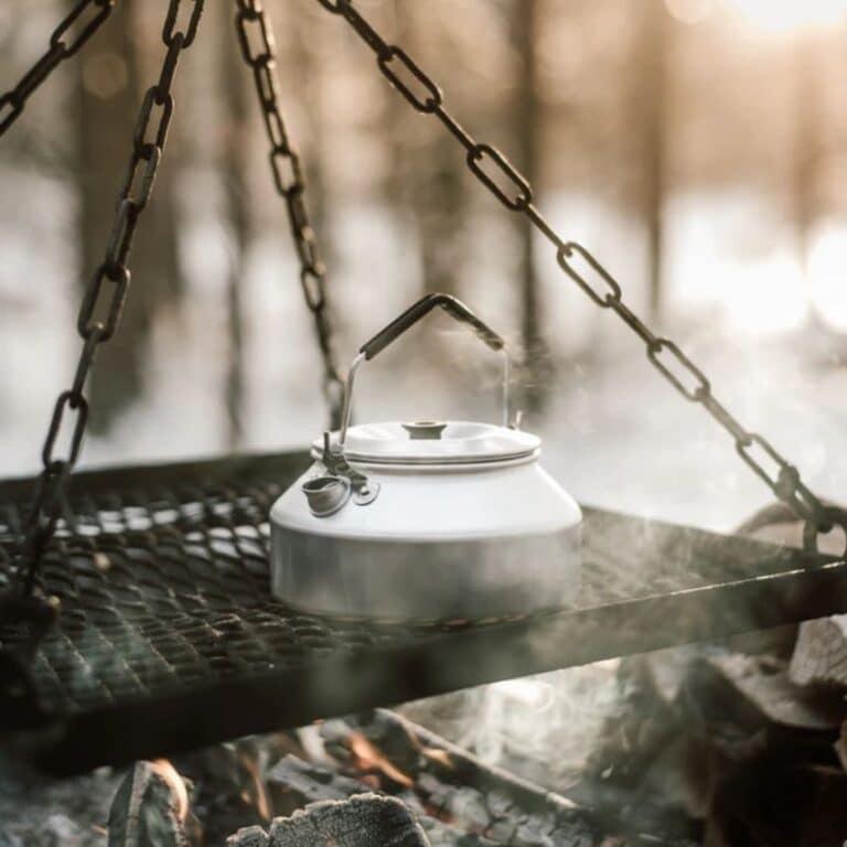 Kedel fra Trangia der koger på et bål