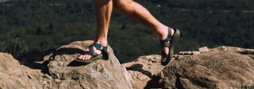 Mand der går med vandresandaler på sten